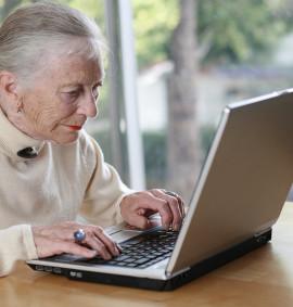 Elderly lady typing on laptop. Shallow DOF.